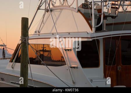 NC01186-00...NORTH CAROLINA - Sinrise colors reflecting in a fishing boat moared at Oregon Inlet Marina on Bodie - Stock Photo