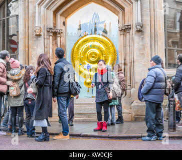 Tourists in front of the the chronophage clock designed by John Taylor at Corpus Christi college, university of - Stock Photo