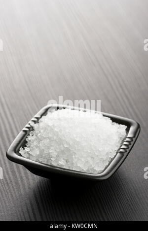natural salt into black bowl on wooden table - Stock Photo