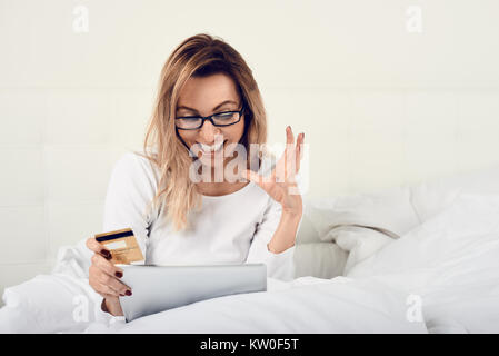 Excited woman making a purchase on a digital tablet holding her credit card in one hand as she stares gleefully - Stock Photo