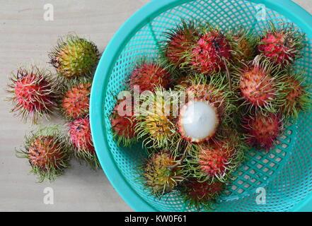 rambutan tropical fruit peel out on plastic basket - Stock Photo