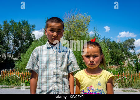 UGUT, KYRGYZSTAN - AUGUST 16: Siblings, brother and a sister posing with serious facial expression. Ugut is a remote - Stock Photo