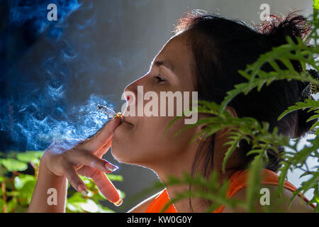 A latin woman smoking, holding a cigarette with her finger and her mouth - Stock Photo