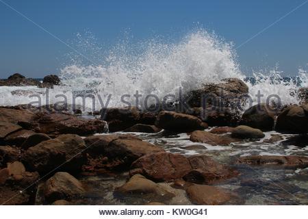 Spray water of Indian ocean waves breaking on red rock - Stock Photo