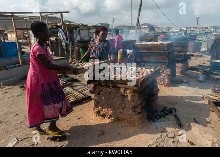 Two women smoking fish over a clay oven, Jamestown Fishing Village, Jamestown, Accra, Ghana, Africa - Stock Photo