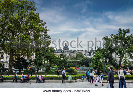 Tourists and locals gather at the Place Jean-Paul II outside the Notre Dame Cathedral on the Ile de la Cite in Paris - Stock Photo