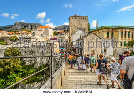 The Mostar bridge over the Neretva River in Bosnia and Herzegovina with tourists heading toward the old town with - Stock Photo