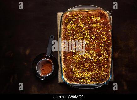 traditional Italian dessert with coffee, cocoa and mascarpone cheese Tiramisu cake in an oven pan on a dark table - Stock Photo