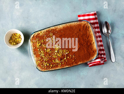 traditional Italian dessert with coffee, cocoa and mascarpone cheese Tiramisu cake in an oven pan on a blue table - Stock Photo