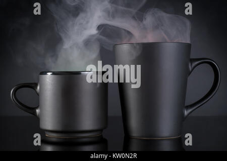 Two black coffee cups with steam. On black background with reflection - Stock Photo