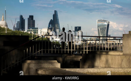 Couple look towards the City of London skyline from a viewing platform on the north bank of the river Thames under - Stock Photo
