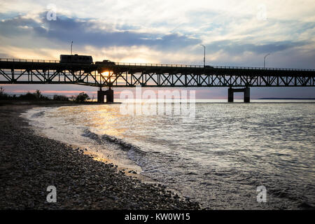 Truck Pulling Camper. Silhouette of a truck pulling a camper across the Mackinaw Bridge at sunset. Mackinaw City, - Stock Photo