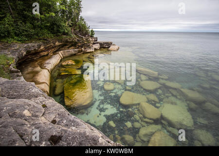 Cliffs On The Seashore. Rocky cliff on the shores of crystal waters of Lake Superior in Michigan's Upper Peninsula. - Stock Photo