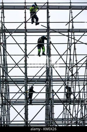 Scaffolders at work, building a large scaffolding, work at high altitude, - Stock Photo