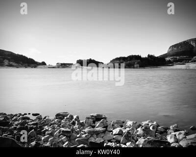 Red house on the rock near the water. The seascape with traditional red white wooden houses on rocky island. - Stock Photo