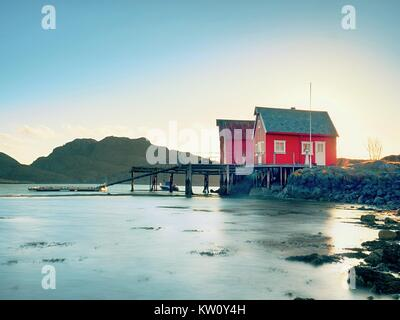 Norwegian coast landscape with a typical red house.  Wooden red house on the seaside, first warm spring day. - Stock Photo
