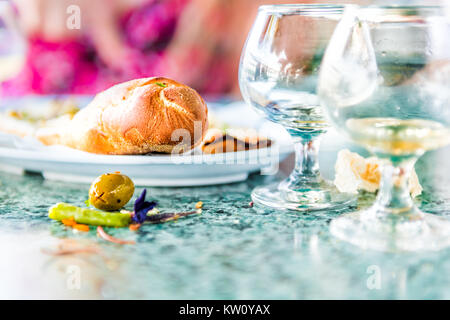 Closeup of leftovers in restaurant on table with small glass cognac whiskey rum glasses and messy dirty surface, - Stock Photo