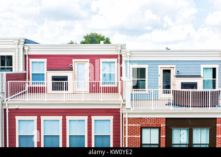 Colorful new modern luxury townhouses with loft on upper level of roof, fireplace, balcony, railing, many windows, - Stock Photo