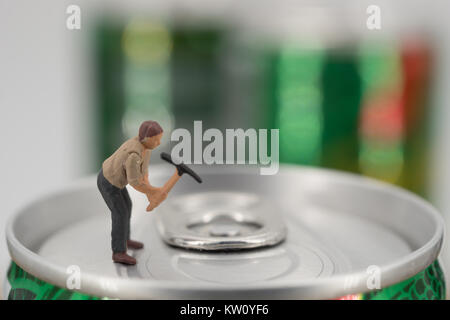 Miniature workman on top of soda can with blurred background. Business concept - Stock Photo