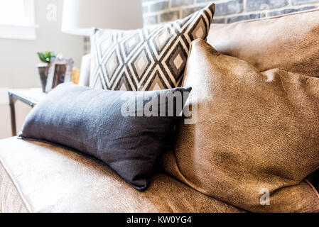 Elegant modern room closeup of leather couch and pillows in staging model house, home or apartment - Stock Photo