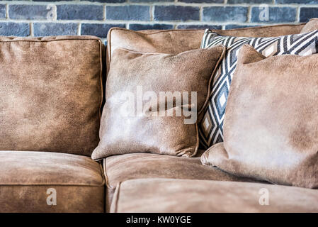 Elegant modern room closeup of leather couch by brick wall in staging model house or apartment - Stock Photo