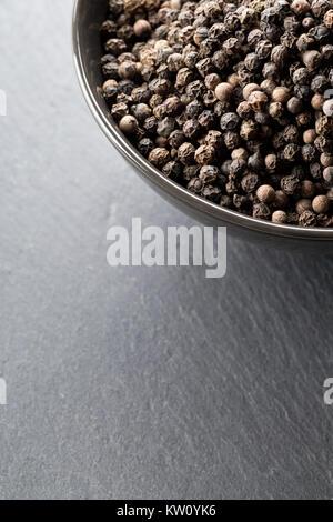 Raw, natural, unprocessed black pepper peppercorns in black bowl on dark stone background - Stock Photo
