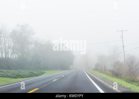 Foggy mist road highway with nobody in rural countryside in West Virginia - Stock Photo