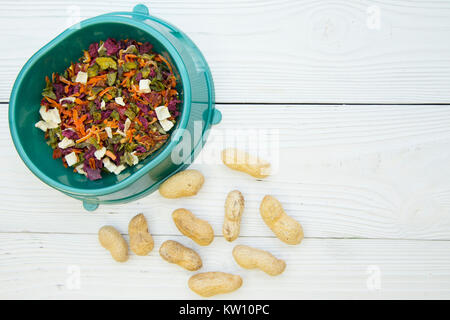 Pet care, veterinary concept. A turquoise plastic bowl with balanced rabbit rodent food-dry green veggies and fruit - Stock Photo