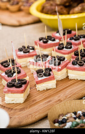 Canapes with sliced black olives, white cheese and salami  on a wooden tray - Stock Photo