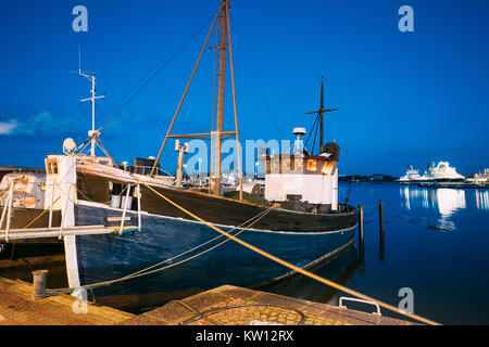 Helsinki, Finland. View Of Fishing Marine Boat, Powerboat At Pier In Evening Night Illuminations. - Stock Photo