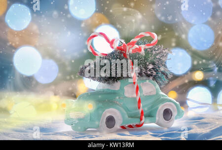 toy car carrying a Christmas tree in night time - Stock Photo