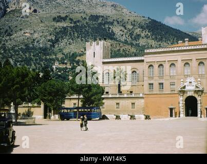 Blue tour bus and tourists outside an elegant building in Monaco, 1952. - Stock Photo