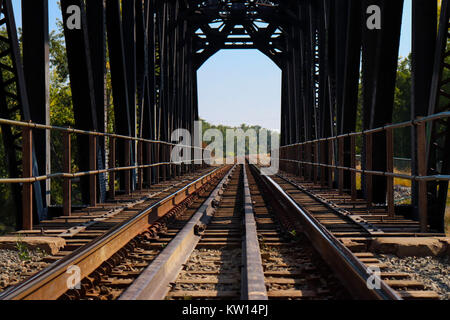 Empty train tracks on a bridge taken from a low angle, blue sky, forest at end - Stock Photo