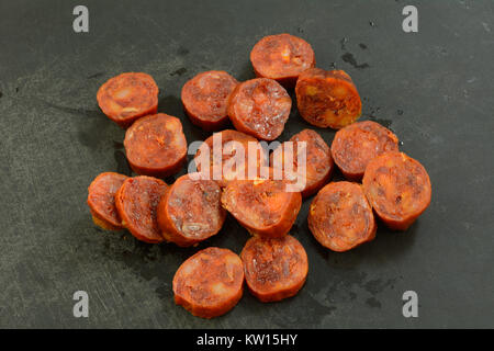 Sliced dried cured chorizo pork sausage on black cutting board as ingredient in preparation for cooking - Stock Photo