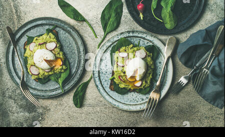 Healthy vegetarian breakfast flat-lay. Whole-grain toasts with avocado, spinach and poached eggs over grey concrete - Stock Photo