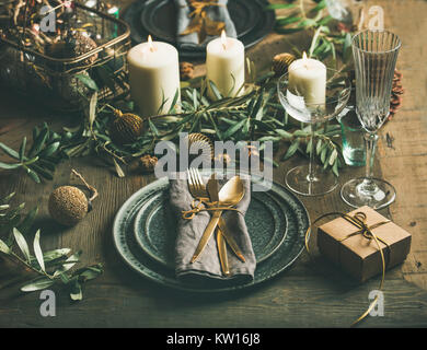 Christmas or New Years celebration party table setting. Plates, golden cutlery, glasses, gift box, festive branch - Stock Photo