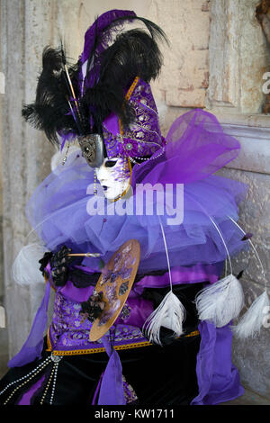 Venice Carnival character in a colorful purple and black Carnival costume and mask Venice Italy - Stock Photo