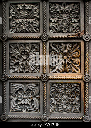 Intricate patterns on an ancient, medieval door to a cathedral. Carved wooden door with floral patterns. Brown-tones - Stock Photo