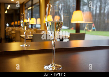 Glass of champagne on the table in the restaurant. - Stock Photo