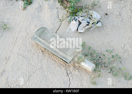 glass bottle on the cracked earth of a low level reservoir - Stock Photo