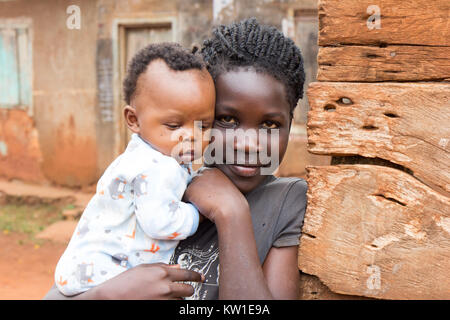 Lugazi, Uganda. June 09 2017. A young African girl holding her baby sister or her child in her arms. - Stock Photo