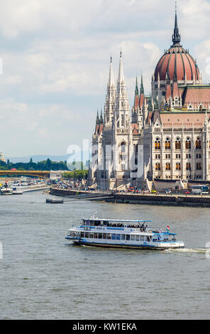 Hungarian Parliament Building, Pest, on the banks of the River Danube and Margaret Bridge and cruise boat from Buda, - Stock Photo