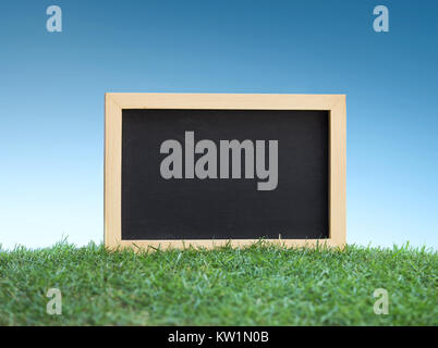 Mini black chalkboard on green grass - Stock Photo