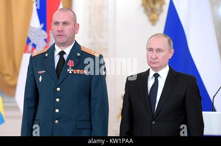 Moscow, Russia. 28th Dec, 2017. Russian President Vladimir Putin stands with Colonel Artur Luft after awarding him - Stock Photo