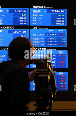 Toyota, Japan. 29th Dec, 2017. A TV crew video tapes a share prices board after a ceremony to celebrate the last - Stock Photo