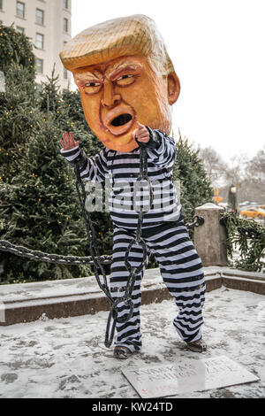 New York, USA, 30 Dec 2017.  A protester wearing a mask mocking a chained US President Donald Trump on a jail uniform - Stock Photo