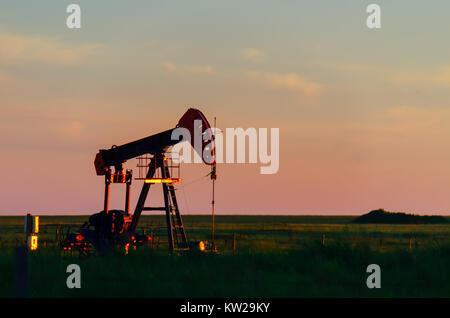 At sunset, oil pumps pour oil on a black field with a pond. Red glow in the background. - Stock Photo