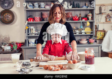 mom helping her son prepare sweet food at home - Stock Photo