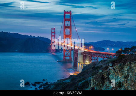 Classic panorama view of famous Golden Gate Bridge seen from scenic Baker Beach in beautiful post sunset twilight - Stock Photo