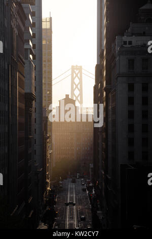 Classic view of historic California Street with famous Oakland Bay Bridge illuminated in first golden morning light - Stock Photo